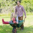 Man pushing his girlfriend in a wheelbarrow — Stockfoto