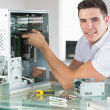 Stock Photo: Handsome cheerful computer engineer working at open computer