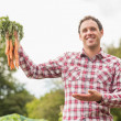 Young man wearing a check shirt presenting some carrots — Stock Photo