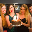 Happy friends celebrating brithday one holding birthday cake — Stock Photo #33442899