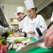 Stock Photo: Four chefs preparing food at counter in a row