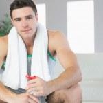 Unsmiling handsome man sitting holding water bottle — Stock Photo #33443305
