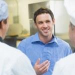 Gerente sonriente joven hablando con el personal — Foto de Stock   #33443511