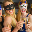 Smiling friends holding champagne glasses wearing masks — Stock Photo #33443703