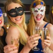 Smiling friends holding champagne glasses wearing masks — Stock Photo