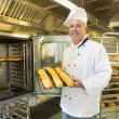 Mature baker showing three baguettes — Stock Photo