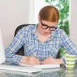 Redhead writing on notepad at her desk — Foto Stock