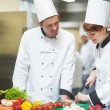Female chef slicing vegetables with colleague — Stockfoto #33444213