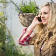 Pretty woman mobile phoning in a green house — Stock Photo #33444285