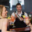 Handsome bartender working while gorgeous friends having cocktails — Stock Photo
