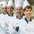Four happy chefs smiling at the camera — Stock Photo