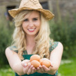 Young blonde woman showing eggs — Stock Photo