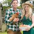 Smiling young couple holding chicken and basket of eggs — Stock Photo
