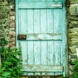 Blue wooden door in a stone wall — Stok fotoğraf