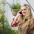 Happy woman mobile phoning in a green house — Stock Photo #33445107