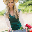 Smiling young female farmer standing at her stall — Stock Photo