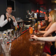 Handsome bartender making cocktails for attractive women — Stock Photo