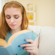 Engrossed redhead reading a book on the couch — Stock Photo