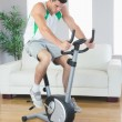 Sporty handsome man training on exercise bike — Stock Photo