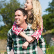 Man giving his beautiful girlfriend a piggyback ride — Stock Photo #33445675
