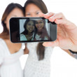 Two smiling asian sisters taking a self portrait — Stock Photo #33446163