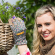 Pretty woman fixing a hanging flower basket — Stock Photo