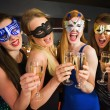 Attractive friends with masks on holding champagne glasses — Stock Photo #33446297