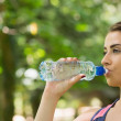 Sporty woman drinking water outdoors — Stock Photo