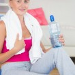 Smiling sporty blonde sitting on exercise mat holding water bottle — Stock Photo #33446415