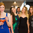Attractive woman holding cocktail standing in front of her friends — Stock Photo #33446447