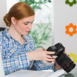 Focused photographer sitting at her desk looking at her camera — Stock Photo