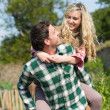 Handsome man giving his girlfriend a piggyback ride — Stock Photo #33446477