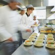 Four chefs working in a modern kitchen — Stock Photo #33446589