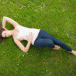 Stock Photo: Beautiful brunette woman lying on grass