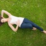 Beautiful brunette woman lying on grass — Stock Photo #33446825