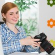 Happy photographer sitting at her desk holding her camera — Stock Photo