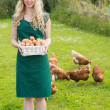 Smiling pretty woman presenting a basket filled with eggs — Stock Photo