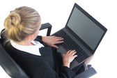Well dressed businesswoman sitting concentrated on her office chair using her laptop — Stock Photo