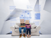 Couple with cartons on head sitting on couch under blue holographic finger print — Stock Photo