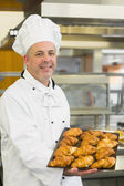 Baker showing some croissants on a baking tray — Foto Stock