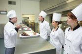 Three chefs presenting their dessert plates to the head chef — Stock Photo