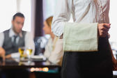 Waitress standing in front of two business people talking — Stock Photo