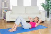 Sporty focused blonde doing sit ups — Stock Photo