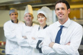 Young restaurant manager posing in front of team — Stock Photo