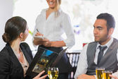 Businesswoman ordering dinner from smiling waitress — Stock Photo