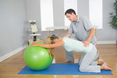 Physiotherapist controlling patient doing exercise with exercise ball — Stock Photo