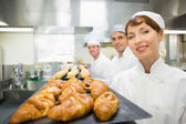 Three young bakers standing in a bakery — Stock Photo