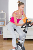 Sporty happy blonde training on exercise bike reading a book — Stock Photo