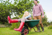 Cheerful man pushing his laughing girlfriend in a wheelbarrow — Stock Photo