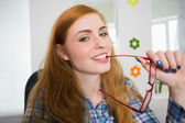 Happy redhead biting her reading glasses — Stok fotoğraf